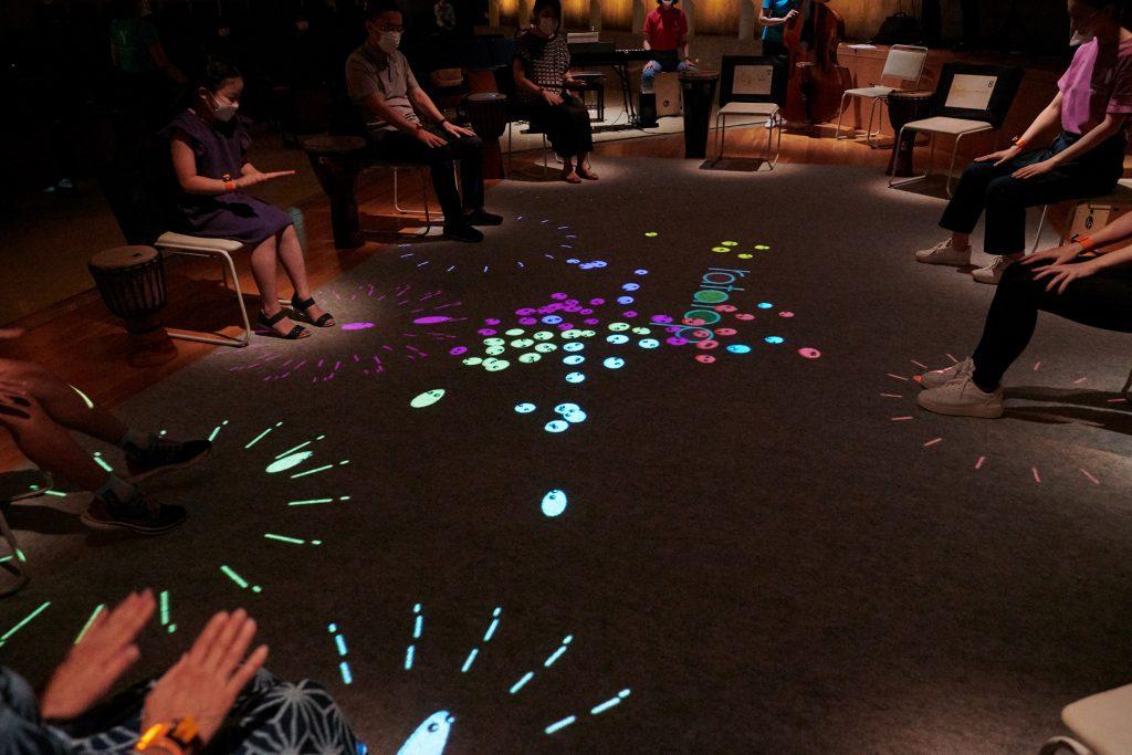 参加者が手を叩くと、その振動によって床に「オトダマくん」が発生。人によって色が異なるため、会場はカラフルな「オトダマくん」で賑やかな雰囲気に
